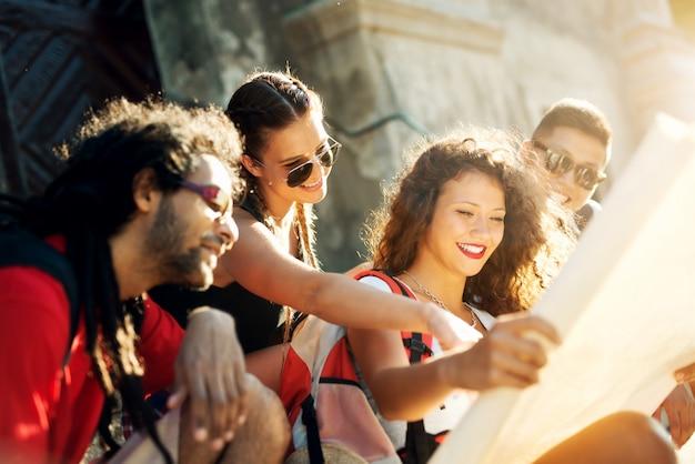 Casais multirraciais explorando uma cidade, turistas felizes descobrindo novos locais olhando o mapa.