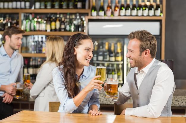 Casais olhando um ao outro, segurando cerveja