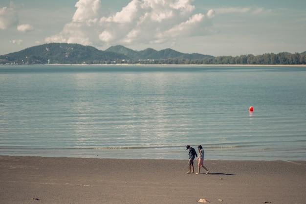 Casais românticos caminhando na praia