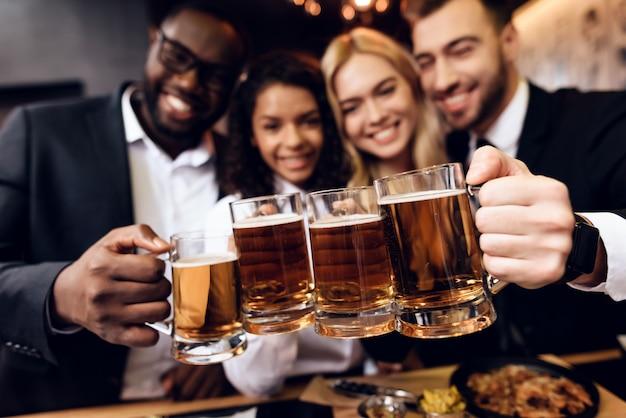 Casais seguram copos de cerveja nas mãos e sorriem.