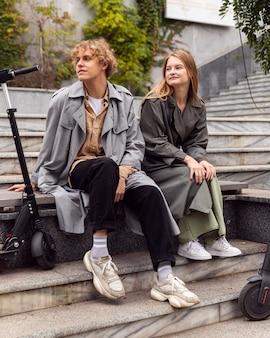 Casais sentados ao ar livre ao lado de scooters elétricos
