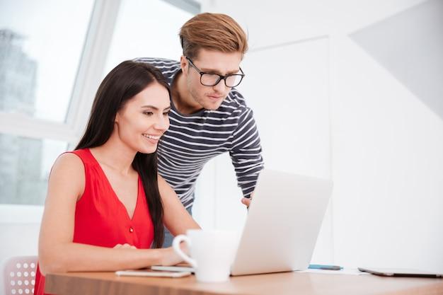 Casal à mesa com o laptop no escritório. mulher sentada na cadeira e homem perto dela