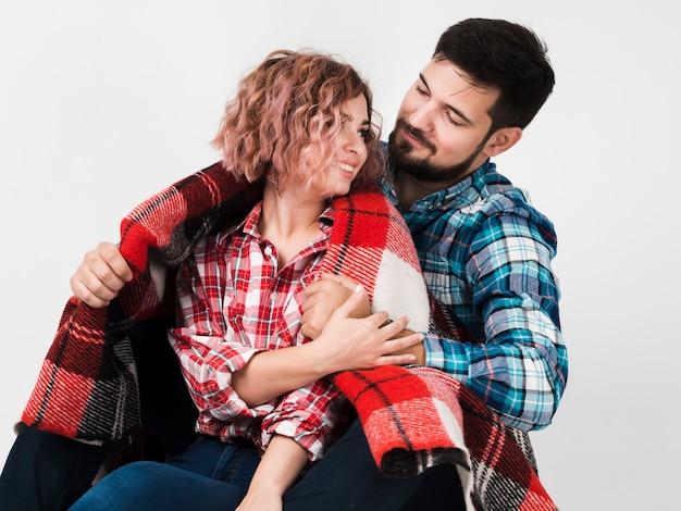 Casal abraçado com cobertor para dia dos namorados