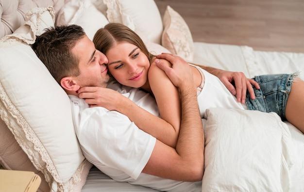 Casal abraçado na cama e sorrindo