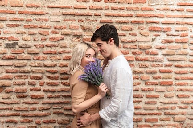 Casal abraçado posando com buquê de lavanda
