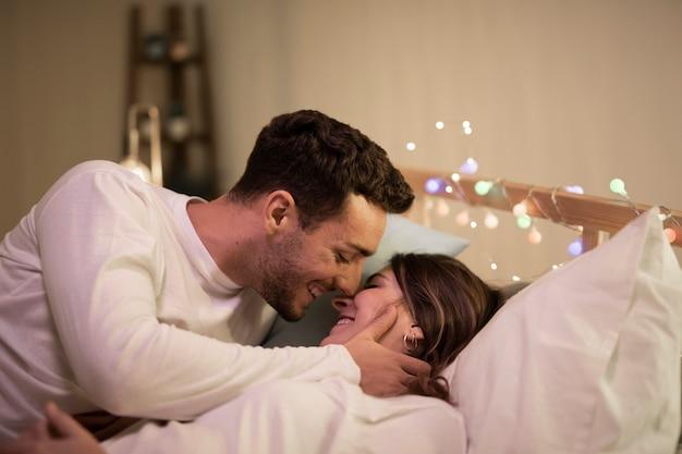 Casal abraçando e beijando na cama