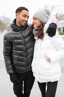Casal abraçando e caminhando juntos no inverno