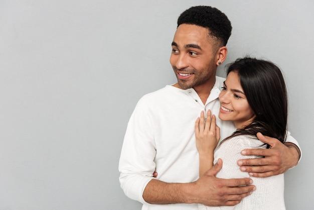 Casal abraçando e olhando para longe
