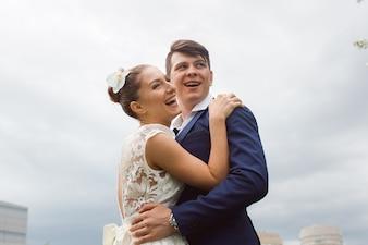 Casal abraçando e rindo no céu
