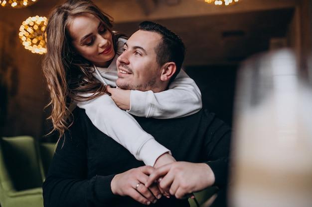 Casal abraçando e sentados juntos dentro de um café