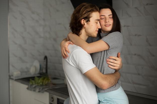Casal abraçando e sorrindo na cozinha