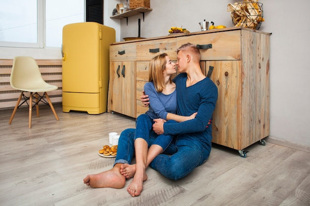 Casal abraçando enquanto está sentado no chão da cozinha
