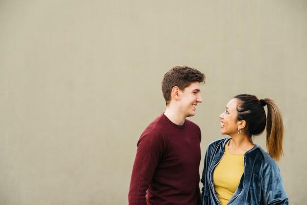 Casal abraçando multiétnica sorrindo e olhando para o outro