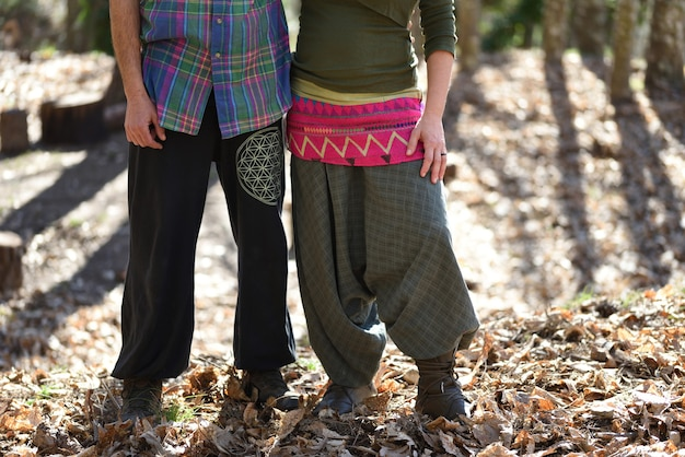 Casal abraçando neo-rural na floresta com roupas coloridas.