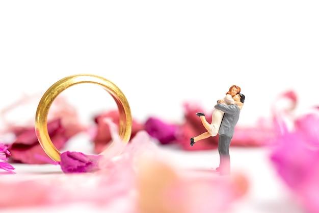 Casal abraço no jardim-de-rosa com um anel de casamento