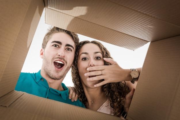 Casal abrindo a caixa de papelão muito feliz