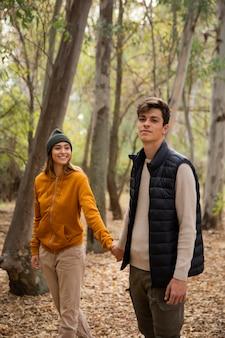 Casal acampando e caminhando na floresta