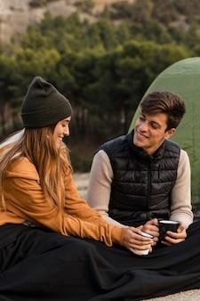 Casal acampando e conversando sobre uma xícara de chá