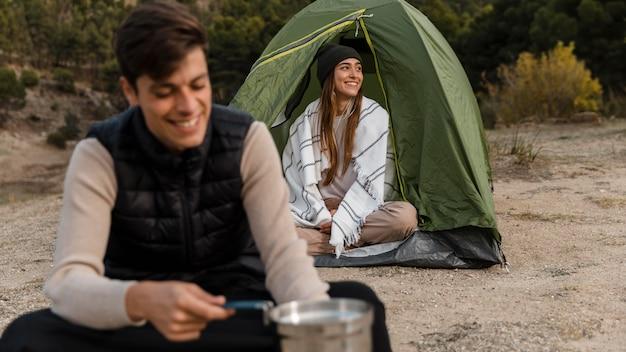 Casal acampando e sendo feliz ao ar livre