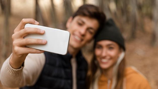 Casal acampando e tirando uma foto