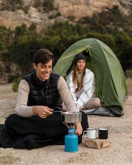 Casal acampando homem cozinhando