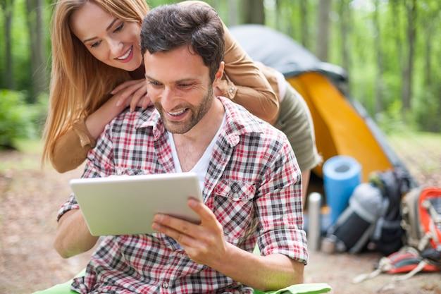 Casal acampando na floresta. casal usando tablet digital na floresta