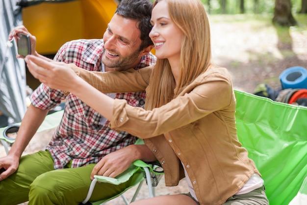 Casal acampando na floresta e tirando uma foto