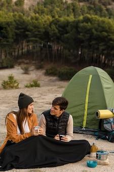 Casal acampando na floresta.