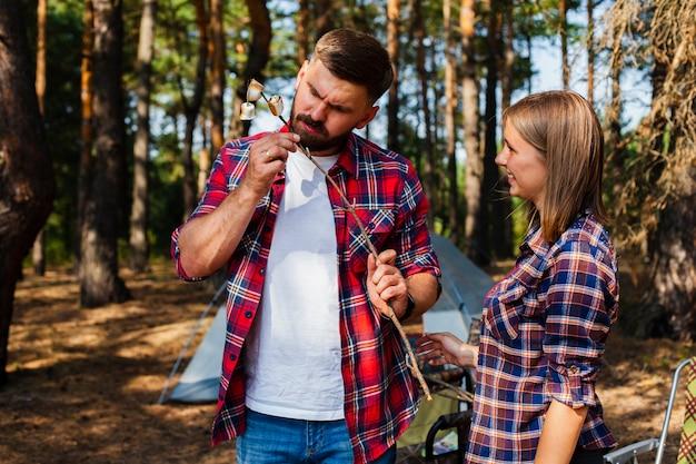 Casal acampar comer marshmellow