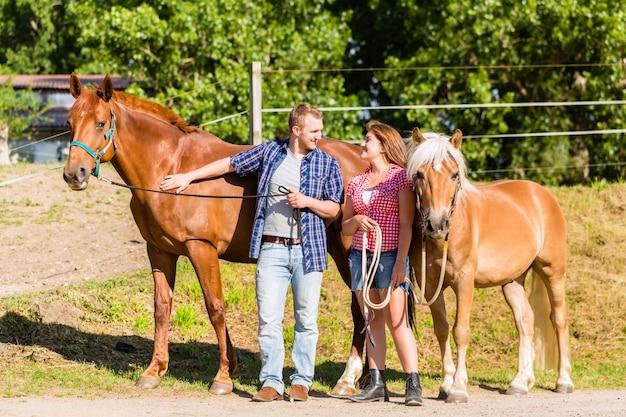 Casal acariciando cavalo no estábulo de pônei
