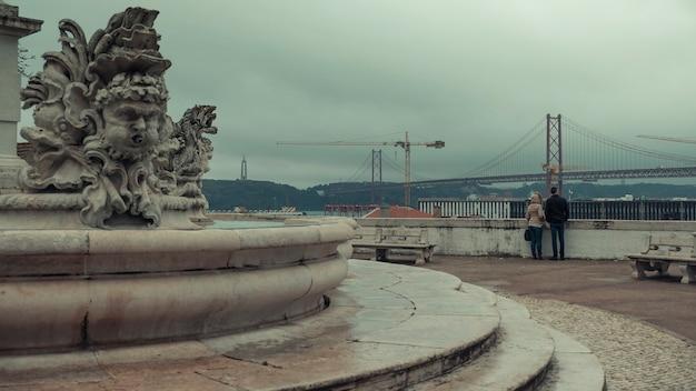 Casal admira a ponte em 25 de abril e a estátua de cristo salvador do deck de observação. fonte antiga com belas esculturas de peixes no miradouro largo das ecessidades lisboa portugal