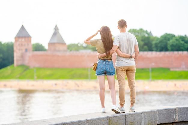 Casal admirando o kremlin de novgorod no rio volkhov