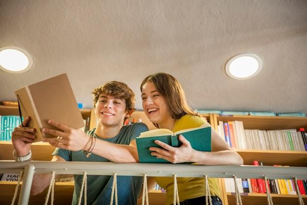 Casal adolescente alegre estudando na biblioteca