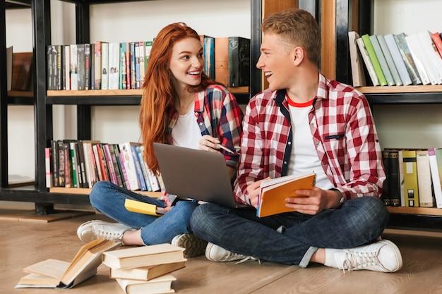 Casal adolescente alegre sentado no chão na estante