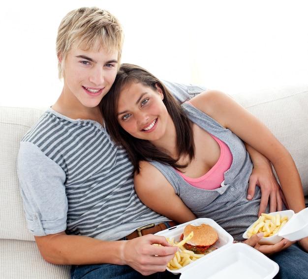 Casal adolescente comendo hambúrgueres e batatas fritas em casa
