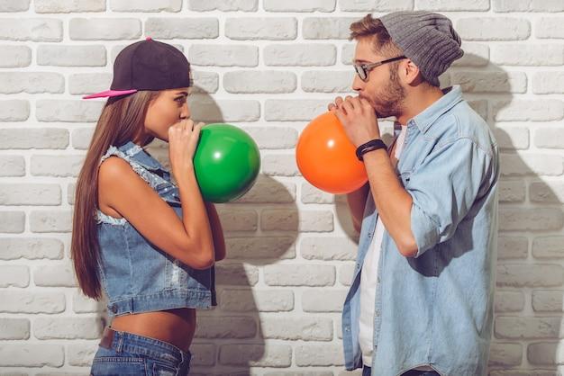 Casal adolescente em roupas jeans e bonés está soprando balões.