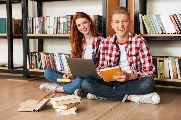 Casal adolescente feliz sentado no chão