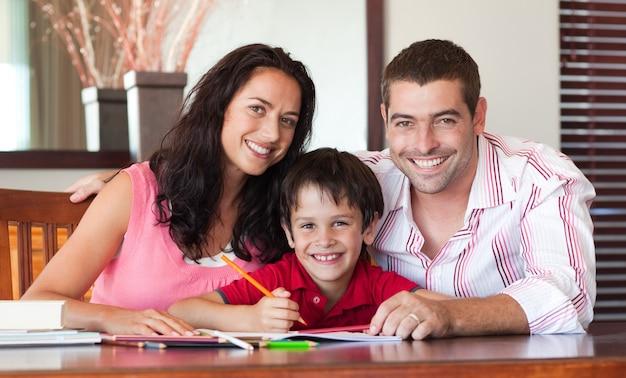 Casal adorável ajudando seu filho a fazer a lição de casa