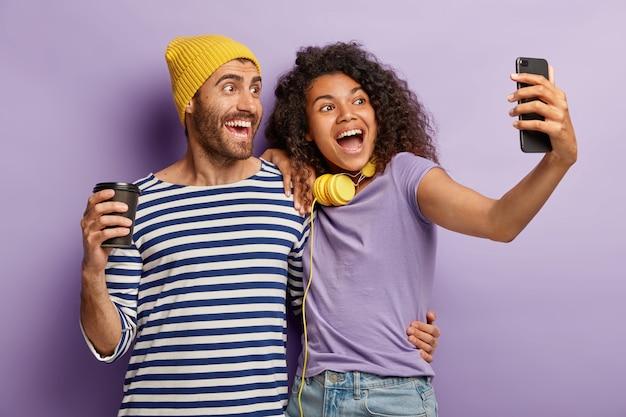 Casal adorável de raça mista se abraça e fique perto, posa para fazer uma selfie, tem expressões alegres, bebe café