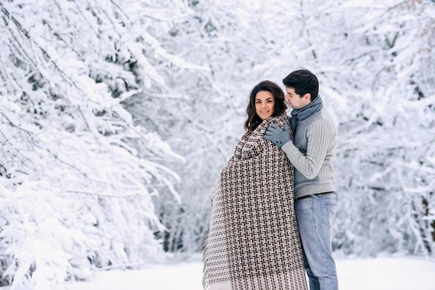 Casal adorável e feliz coberto com um cobertor quente e caminhando em um parque nevado