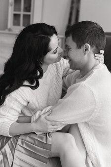 Casal adorável em suéteres brancos aconchegantes posando em casa durante a época do natal