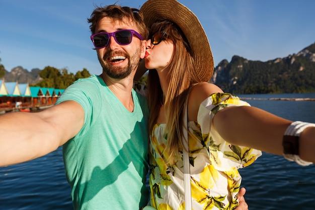 Casal adorável feliz fazendo selfie de férias nas montanhas e lago, chapéu e óculos de sol com roupas brilhantes de verão, beijos e diversão juntos.