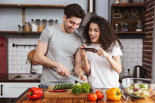 Casal adorável homem e mulher cozinhando salat com legumes juntos em uma cozinha moderna em casa