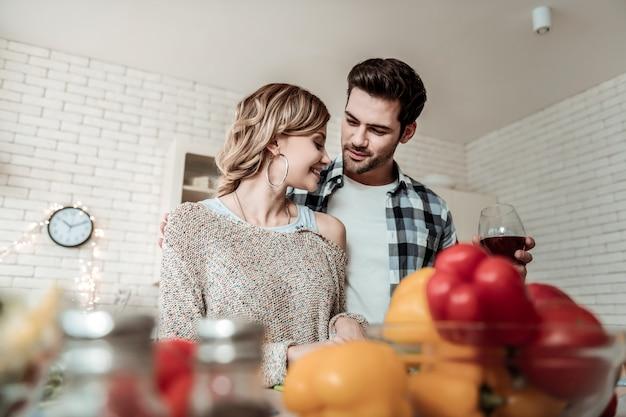 Casal adorável. mulher jovem e sorridente com brincos grandes e o marido se sentindo bem enquanto cortam verduras juntos