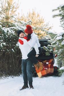 Casal adorável no carro da floresta de inverno nas costas ao fundo