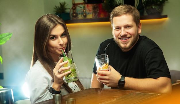 Casal adorável relaxando no bar com coquetéis