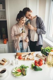 Casal adorável sorrindo enquanto bebe suco fresco e come vegetais na cozinha