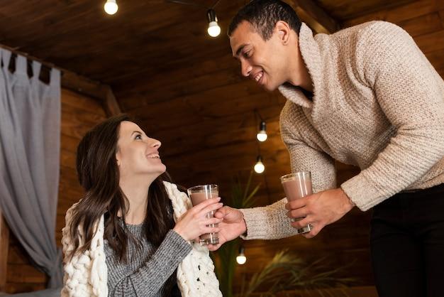 Casal adorável tomando bebidas quentes