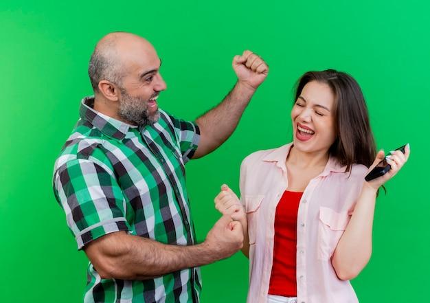 Casal adulto alegre em pé na vista de perfil. mulher segurando um telefone celular com os olhos fechados. ambos os punhos cerrados isolados na parede verde