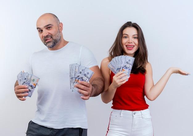Casal adulto alegre segurando dinheiro mulher mostrando as mãos vazias olhando